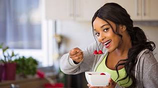 A smiling lady is eating a bowl of strawberries.