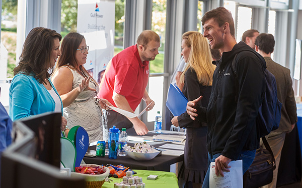 Students and employers engage in conversation at a career fair.