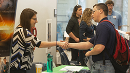 A professional member of the community shaking hands with a student at a career fair