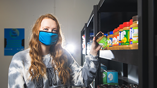 A student collects groceries items at the campus pantry location.