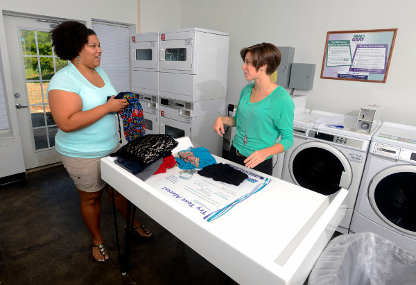 Two students folding laundry in the laundry room