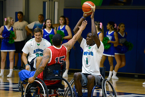 Staff and community members play basketball in wheelchairs to raise awareness for individuals living with disabilities.
