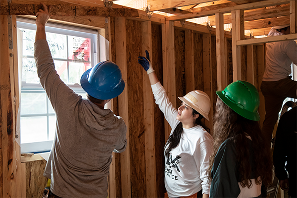 Three students work together to install window in Habit for Humanity home.