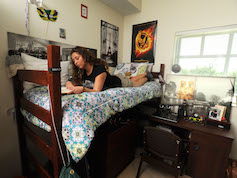 Student lying on bed in suite-style double room
