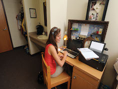 Student sitting at desk in residence hall room.
