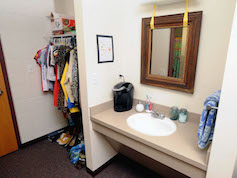 A traditional-style residence hall sink and mirror.