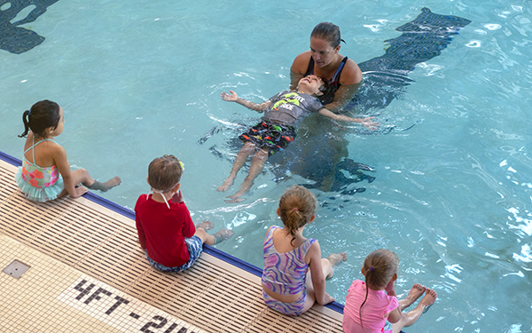 A child is learning to float on his back with help from the swim instructor during a swim lesson.
