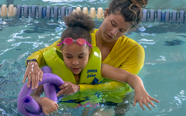 A swim instructor helping a participant stay afloat.