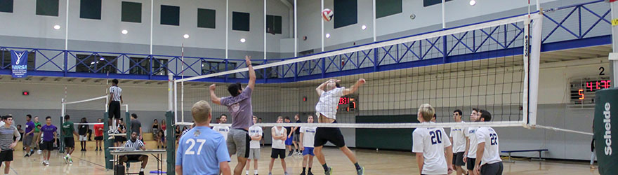 Students participating in Intramural Sports Volleyball tournament: two students on either side of the net are jumping for the volleyball.