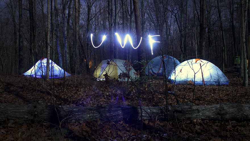 At night tents are set up with lights inside of them. Students are spelling out UWF OA using lights outside of the tents.