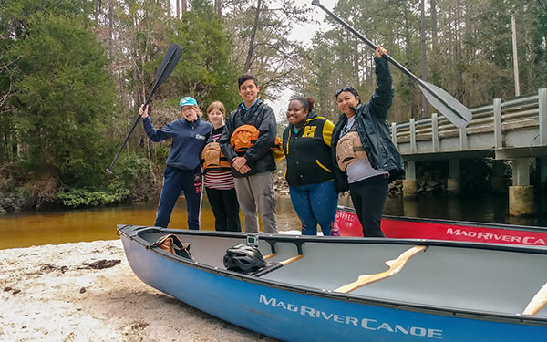 Participants on the canoe trip posing together, holding up canoe oars and smiling at the camera.