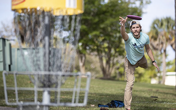 Student throwing a disc towards the basket on the UWF disc gold course