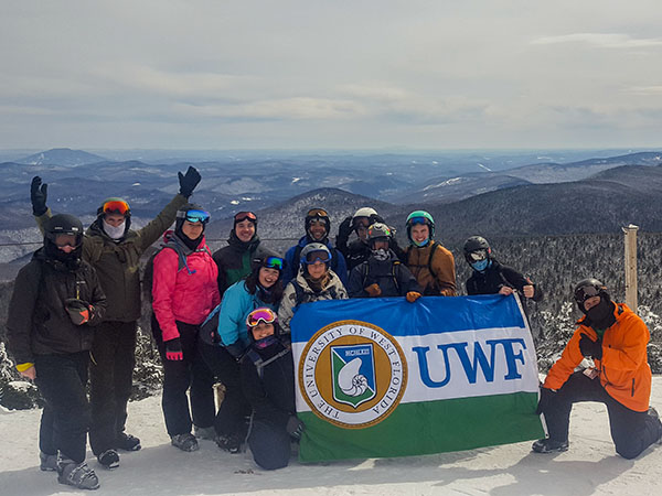 Spring Break Ski Trip Group photo; the students are holding up the UWF flag