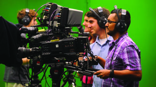Students work behind the camera in a media lab.