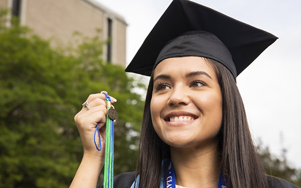 A UWF graduate in cap and gown holds up a tassel.