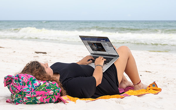 A UWF student uses a laptop while lying on Pensacola Beach.