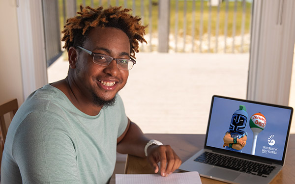 A UWF student smiles and writes with pen and paper by a laptop at home.
