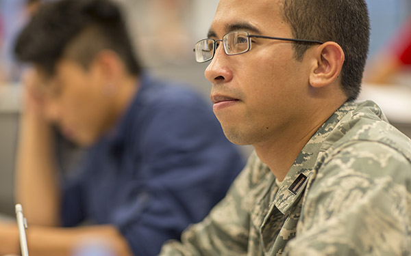A UWF student in military uniform listens in class.