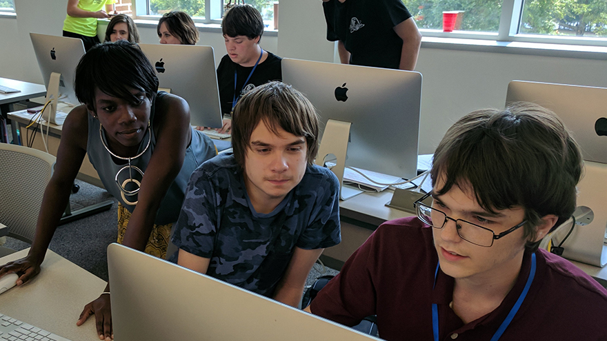 students at cybersecurity camp working out a problem on a computer