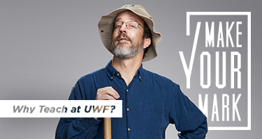 Dr John Worth in a floppy hat and dark blue shirt poses against a light gray background saying