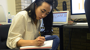 A student sits and writes in a notebook.