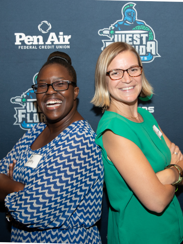 Two alumnae pose back to back at a recent alumni event.