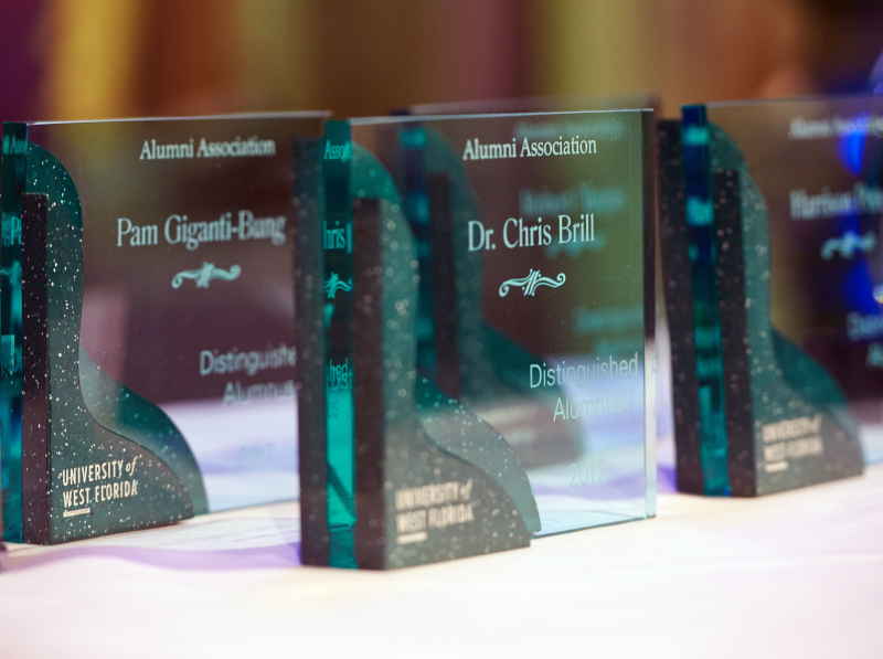 Green, glass rectangular awards are displayed on a table before the 2017 Alumni Awards ceremony.