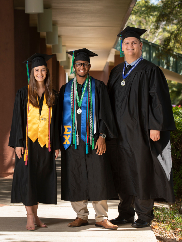 Three graduates pose on campus by Building 21.