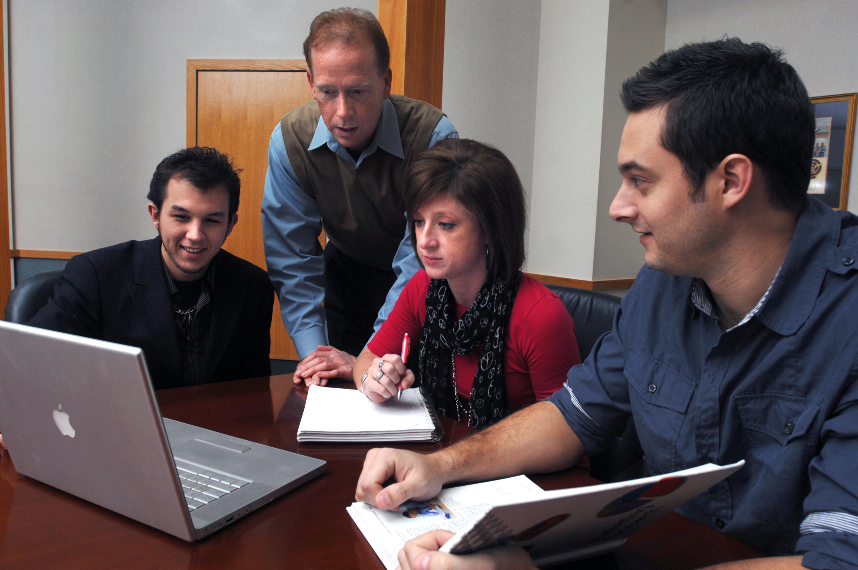 group of students viewing information on a laptop during class