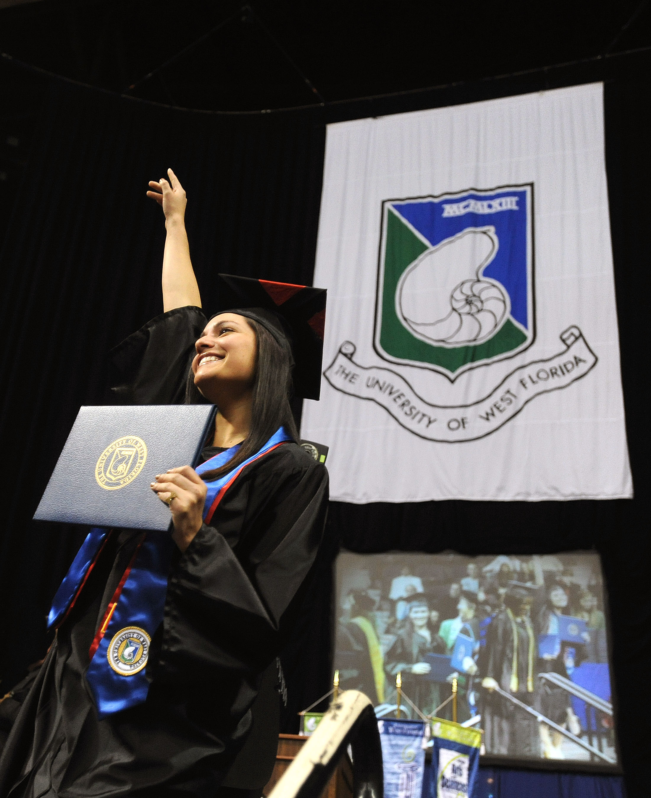 student proudly displaying her diploma cover during commencement ceremony