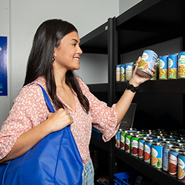 student selecting some canned food from the pantry shelves