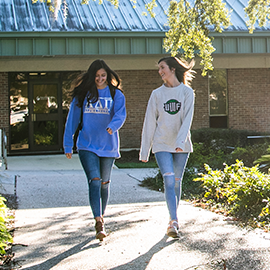 two students walking and talking on campus