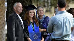 Female graduate is in her cap and gown holding her diploma and posing for a picture with her parents.