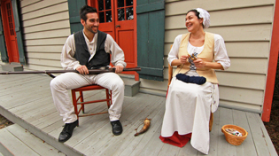 A male and female historical reenactor are sitting in chairs on the porch of the Lavalle House.